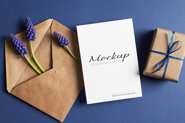 Invitation or greeting card mockup with gift box, envelope and blue muscari flowers