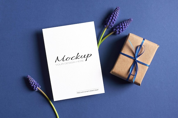 Invitation or greeting card mockup with gift box and spring blue muscari flowers