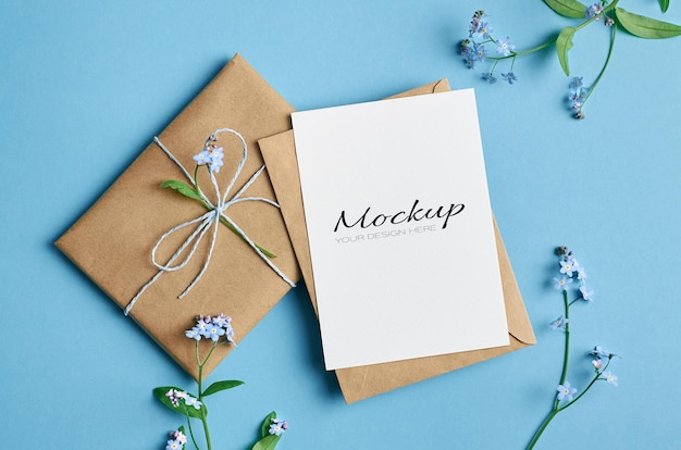 Invitation or greeting card mockup with gift and spring forget-me-not flowers on blue