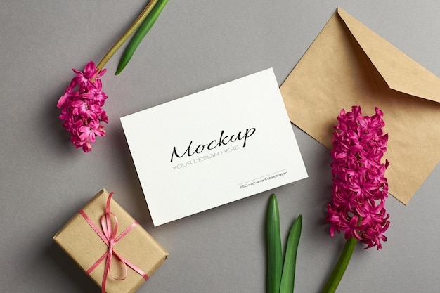 Invitation or greeting card mockup with hyacinth flowers, envelope and gift box on grey