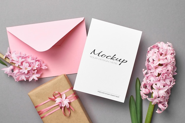 Invitation or greeting card mockup with pink envelope, gift box and hyacinth flowers