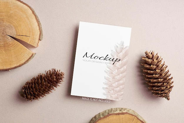 Invitation or greeting card sationary mockup with fir-tree cones and cut log decorations