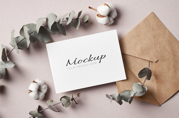 Invitation or greeting card stationary mockup with envelope and dry eucalyptus and pure cotton flowers