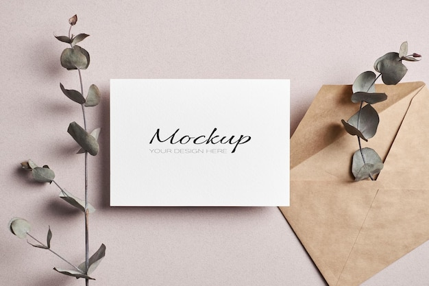 Invitation or greeting card stationary mockup with envelope and dry eucalyptus twigs