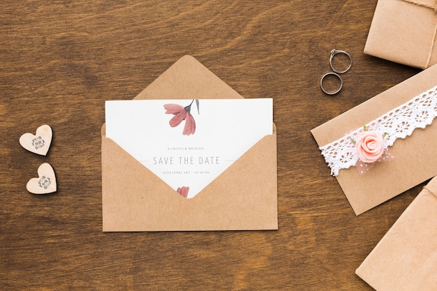 Invitation mock-up and wedding rings on wooden background