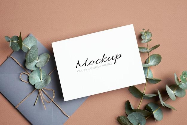 봉투와 유칼립투스 나뭇 가지가있는 초대 또는 인사말 카드 모형