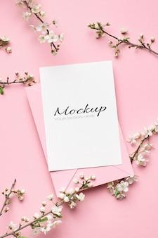 Макет приглашения или поздравительной открытки с конвертом и ветками весеннего дерева с цветами