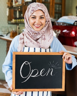 Islamic woman small business owner holding blackboard with smile