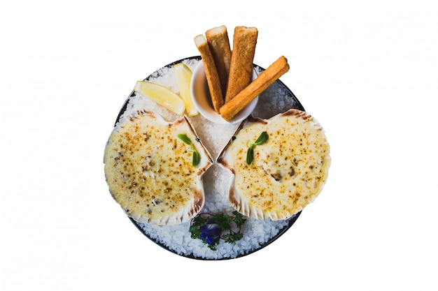 Isolated top view of baked scallops with cheese served with sliced lemon and bread sticks.
