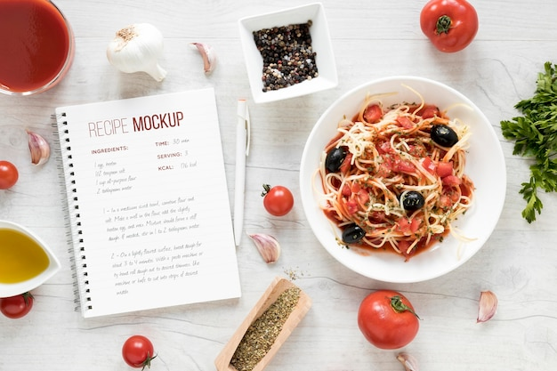 Italian food arrangement with notebook mock-up