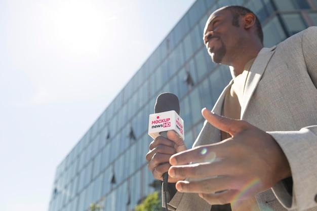 Журналист держит макет микрофона