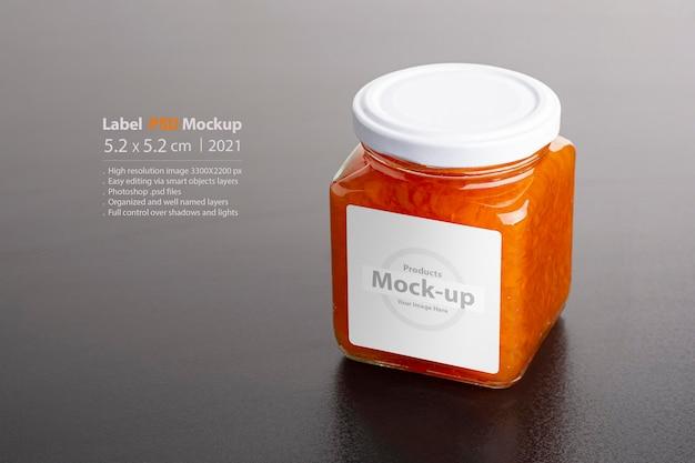 スマートオブジェクトレイヤーと黒いテーブル編集可能なモックアップシリーズのガラス瓶にジューシーな自家製ニンジンジャム