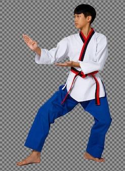 Мальчик-подросток каратэ практикует удар в черном поясе, униформе тхэквондо, во всю длину, изолирован