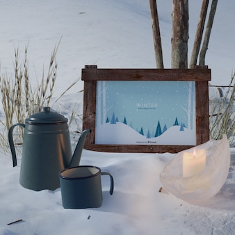 Kettle and cup beside frame with winter theme