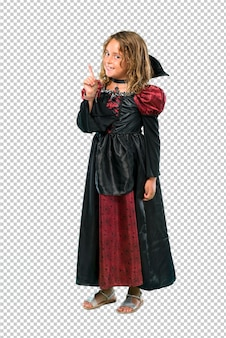 Kid dressed as a vampire at halloween holidays counting number one sign