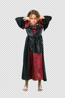 Kid dressed as a vampire at halloween holidays covering both ears with hands