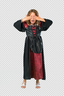 Kid dressed as a vampire at halloween holidays covering eyes by hands