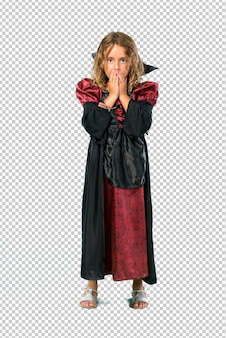 Kid dressed as a vampire at halloween holidays covering mouth with hands