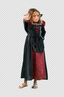 Kid dressed as a vampire at halloween holidays making stop gesture with her hand