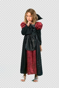 Kid dressed as a vampire at halloween holidays showing a sign of closing mouth and silence gesture
