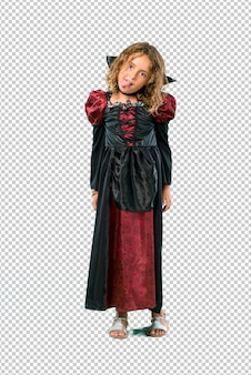 Kid dressed as a vampire at halloween holidays showing tongue at the camera having funny look