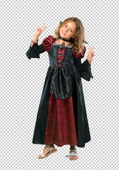Kid dressed as a vampire at halloween holidays smiling and showing victory sign