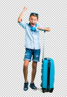 Kid with sunglasses and headphones traveling with his suitcase celebrating a victory