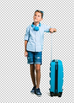 Kid with sunglasses and headphones traveling with his suitcase having doubts