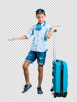 Kid with sunglasses and headphones traveling with his suitcase holding copyspace imaginary