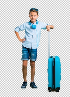 Kid with sunglasses and headphones traveling with his suitcase posing with arms at hip