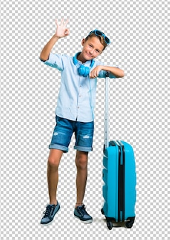 Kid with sunglasses and headphones traveling with his suitcase showing an ok sign with fingers