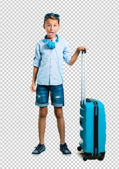 Kid with sunglasses and headphones traveling with his suitcase showing tongue at the camer