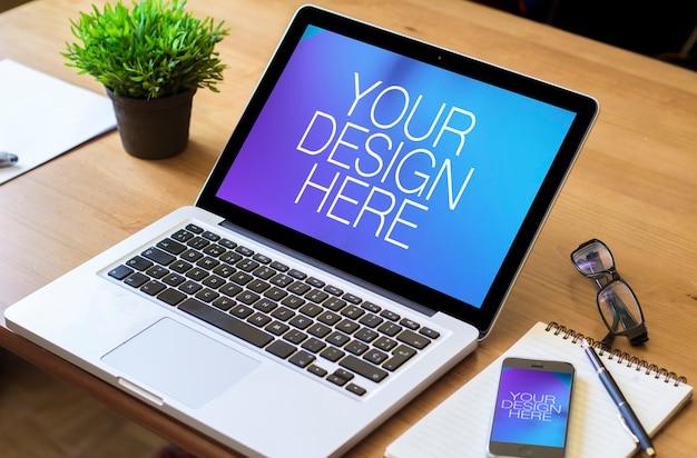 オフィスのテーブルの上のノートパソコンと携帯電話のモックアップ