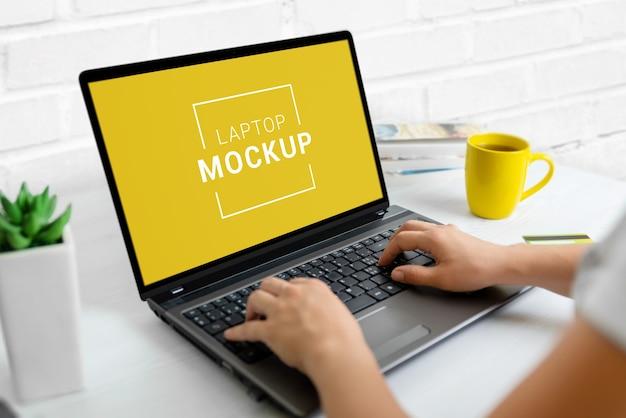 仕事机の上のノートパソコンのクローズアップのモックアップ