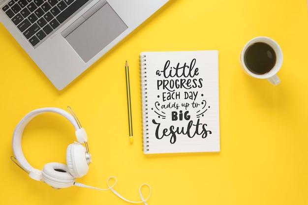 Ноутбук кофе наушники и блокнот на желтом фоне