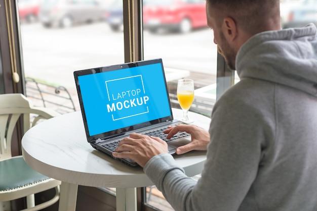 コーヒーショップでフリーランサーが実行するラップトップモックアップ