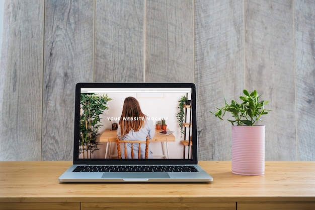 Laptop mockup on table with plants