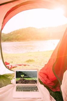 Modello di laptop con il campeggio nel concetto di natura