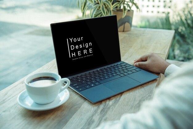 Макет ноутбука с кофе на столе на улице