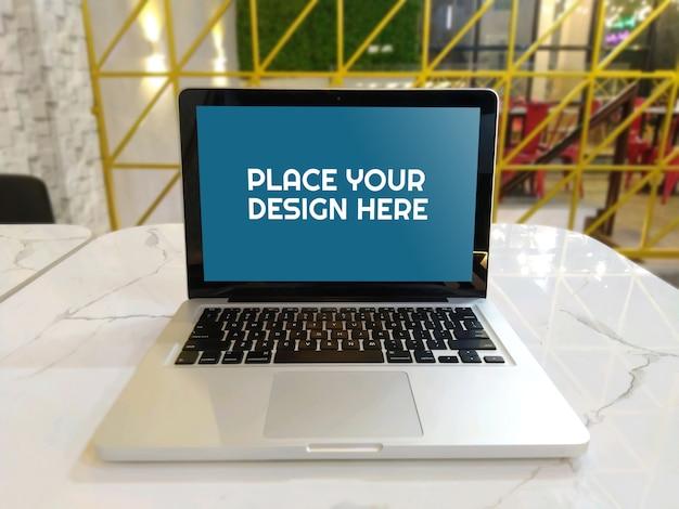 コーヒーショップのモックアップのテーブルの上のノートパソコン