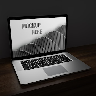 Laptop screen mockup in the dark on wooden desk