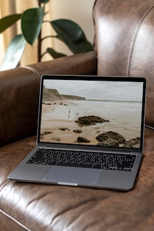 Laptop screen mockup psd on a leather couch