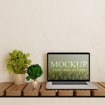Laptop screen mockup on wooden wall desk with plants