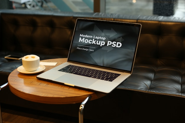 Laptop with coffee on round table mockup psd
