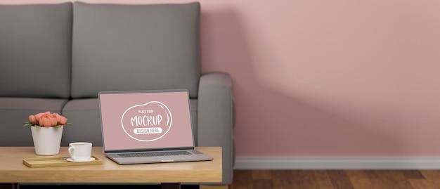ソファの装飾とピンクの壁のあるリビング ルームのコーヒー テーブルにモックアップ画面を備えたラップトップ