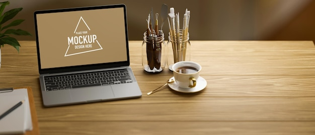 Laptop with mock-up screen on wooden table with paint tools and coffee cup, 3d rendering, 3d illustration