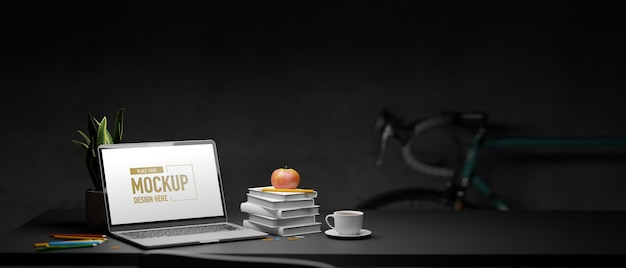 Laptop with mockup screen and stack of books