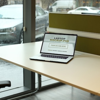 Laptop on workplace table at office mockup psd