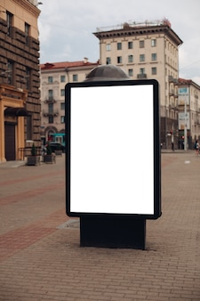 A large billboard with interesting information and advertising on it installed along a wide street in the city center