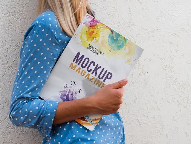 Боковой вид женщина держит макет журнала